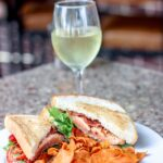 club sandwich, white wine, and chips